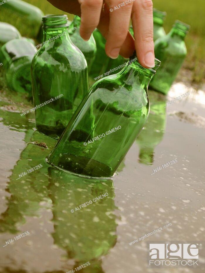 Stock Photo: Hand grabbing a bottle.
