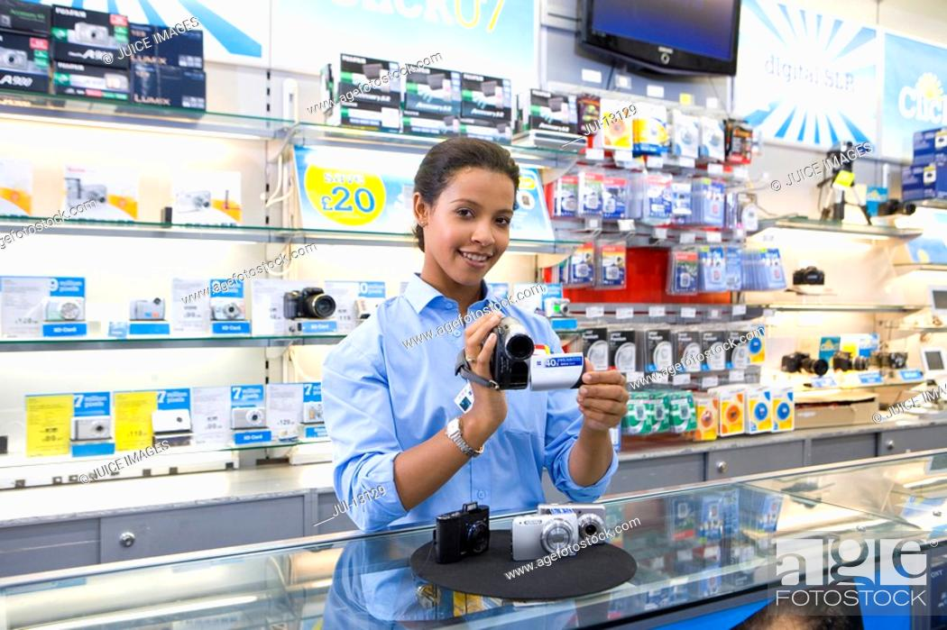 Stock Photo: Young saleswoman with video camera, smiling, portrait, low angle view.