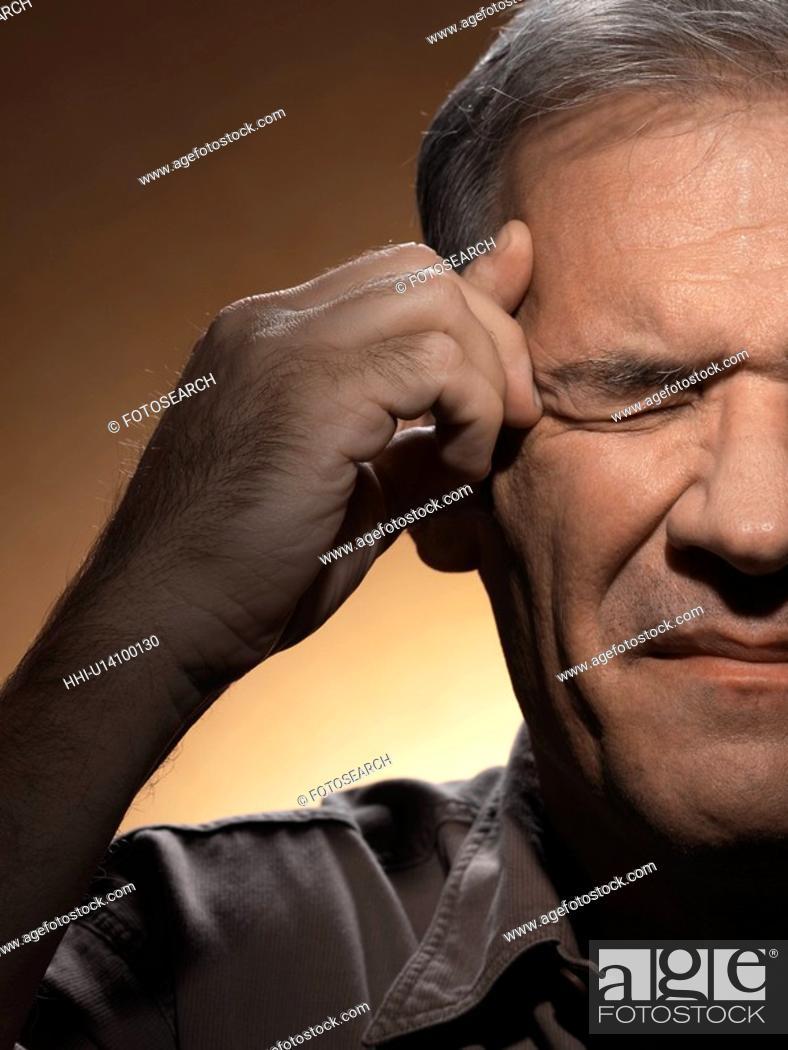Stock Photo: Man rubbing forehead.