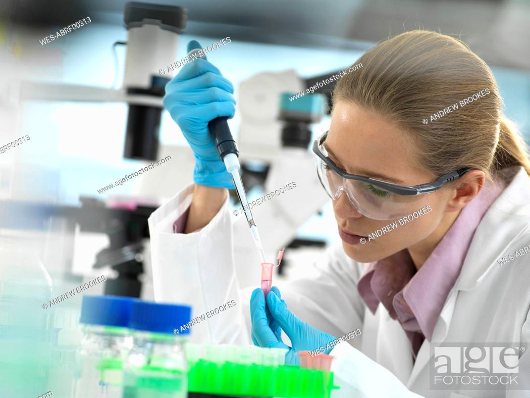 Stock Photo: Scientist pipetting sample into a vial ready for automated analysis in the laboratory.