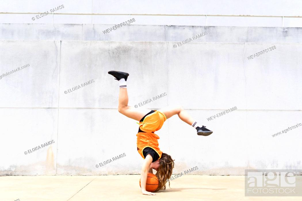 Stock Photo: Teenage girl doing acrobatics with basketball outdoors.