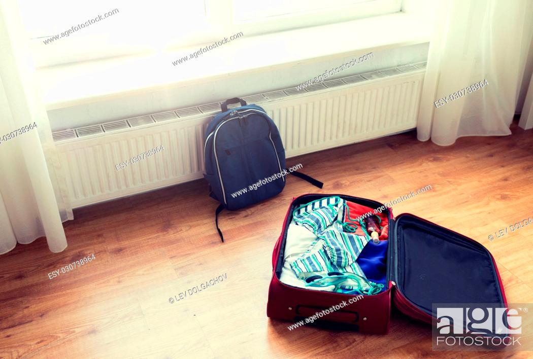 Stock Photo: summer vacation, travel, tourism and objects concept - close up of travel bag with beach clothes and backpack on floor at home or hotel room.