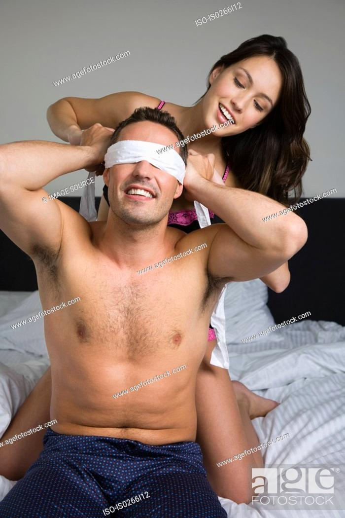 Stock Photo: A woman blindfolding a man.