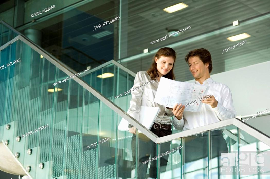 Stock Photo: Low angle view of a businessman showing a blueprint to a businesswoman.
