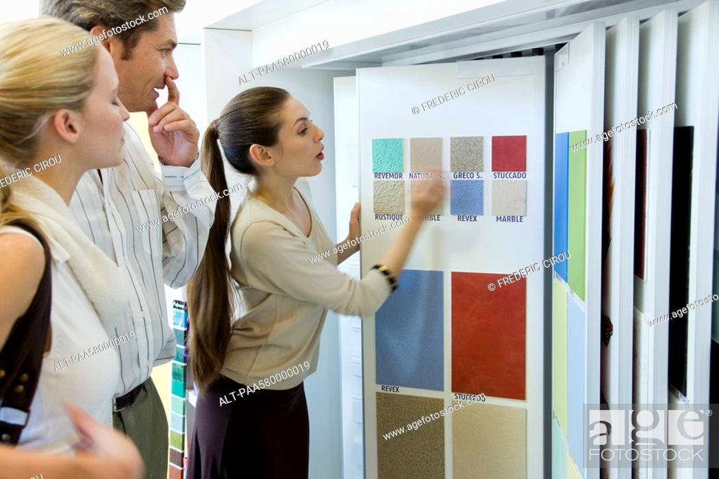 Stock Photo: Woman assisting couple choosing color samples in store.