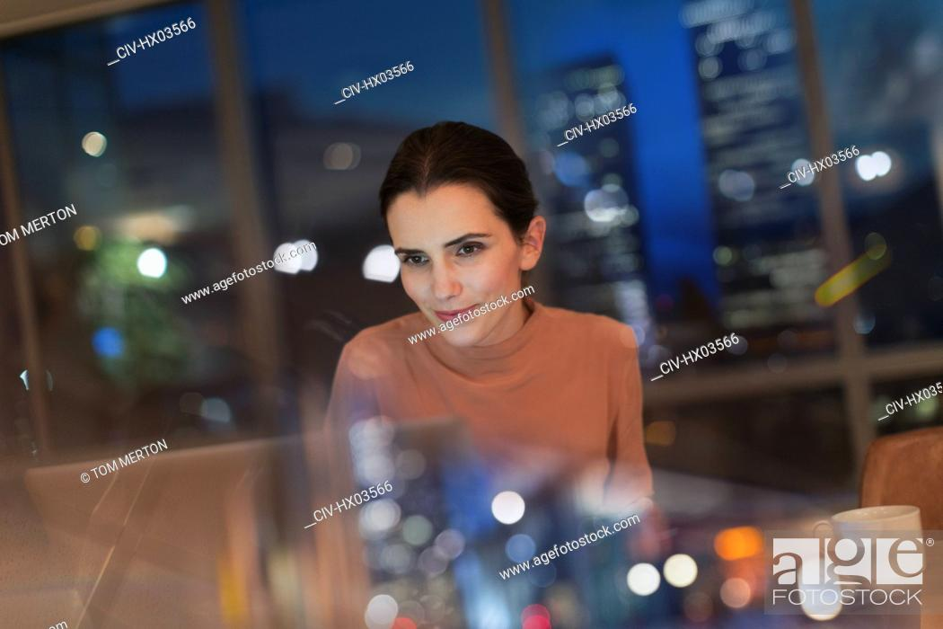 Stock Photo: Businesswoman working late at laptop in office at night.