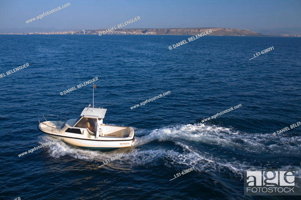 Stock Photo: Fishing boat going back to the harbor. Santa Pola in background, Tabarca island. Alicante province. Spain.