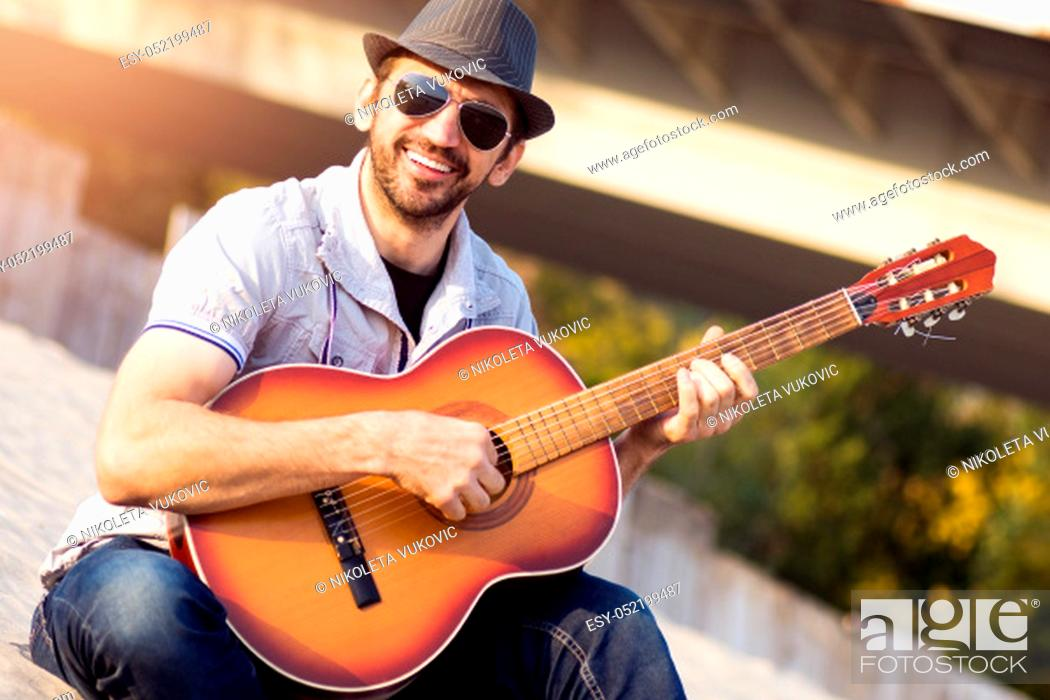 Stock Photo: The smiling fashionable hipster guy in hat and sunglasses is playing guitar outdoors.