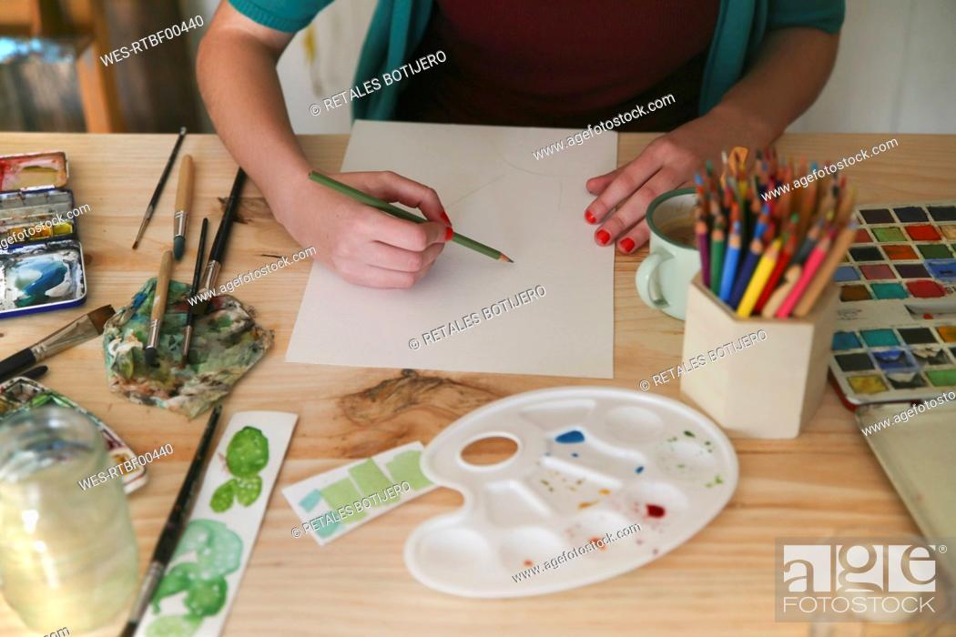 Photo de stock: Woman's hand drawing with green pencil on paper.