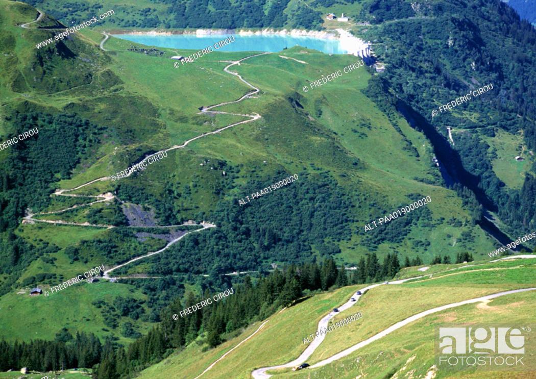 Stock Photo: France, Savoie, roads through mountains, one leading to blue lake.