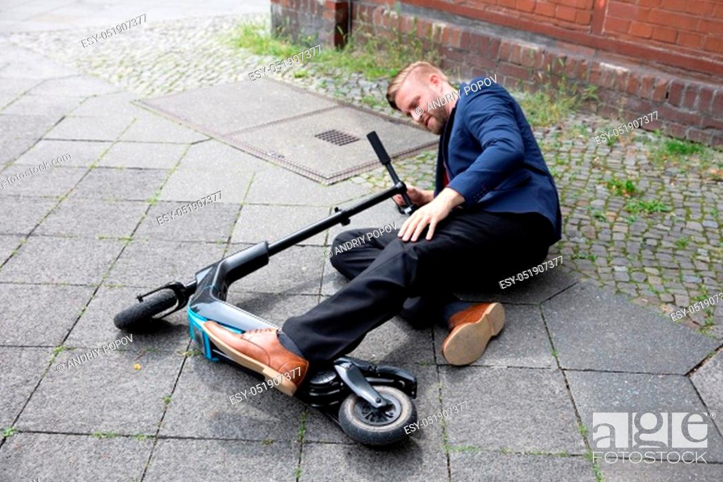 Stock Photo: Young Man Accident With An Electric Scooter On Street.
