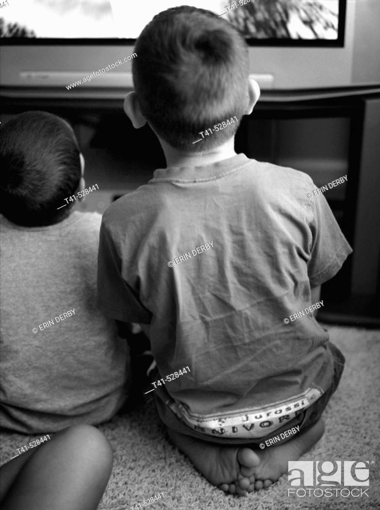 Stock Photo: Two brothers sit side by side as they play video games.