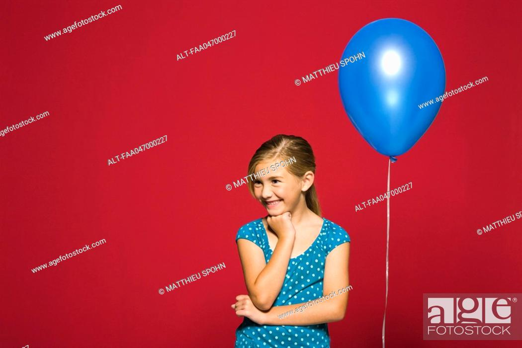 Stock Photo: Girl with hand under chin, balloon suspended behind her.