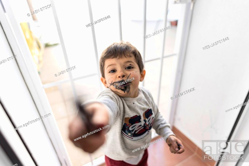 Stock Photo: Little boy showing crayon after painting his face.