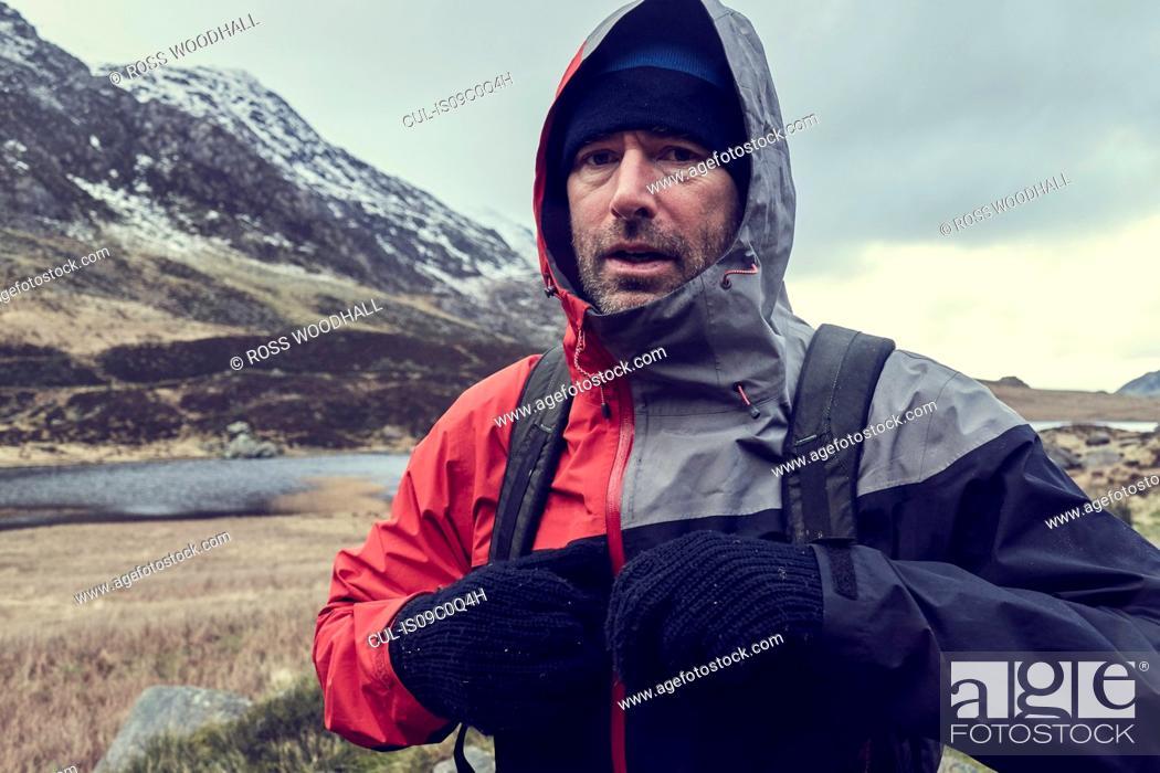 Imagen: Male hiker with hood up in snow capped mountain landscape, portrait, Llanberis, Gwynedd, Wales.