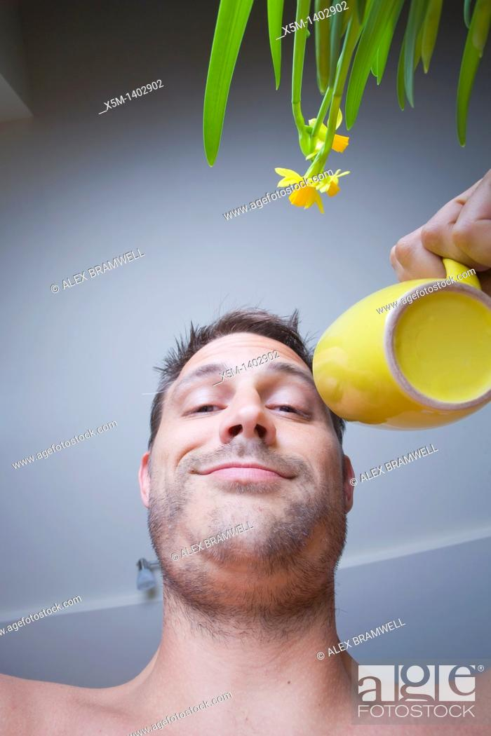 Stock Photo: Man in his kitchen drinking coffee from a yellow mug.