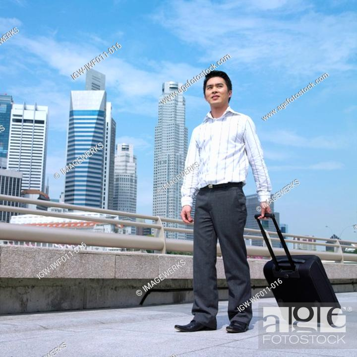 Stock Photo: Low angle view of a businessman holding a suitcase.