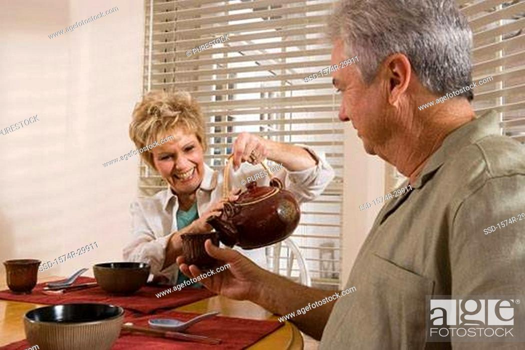 Stock Photo: Mature couple by breakfast table pouring tea into a cup.
