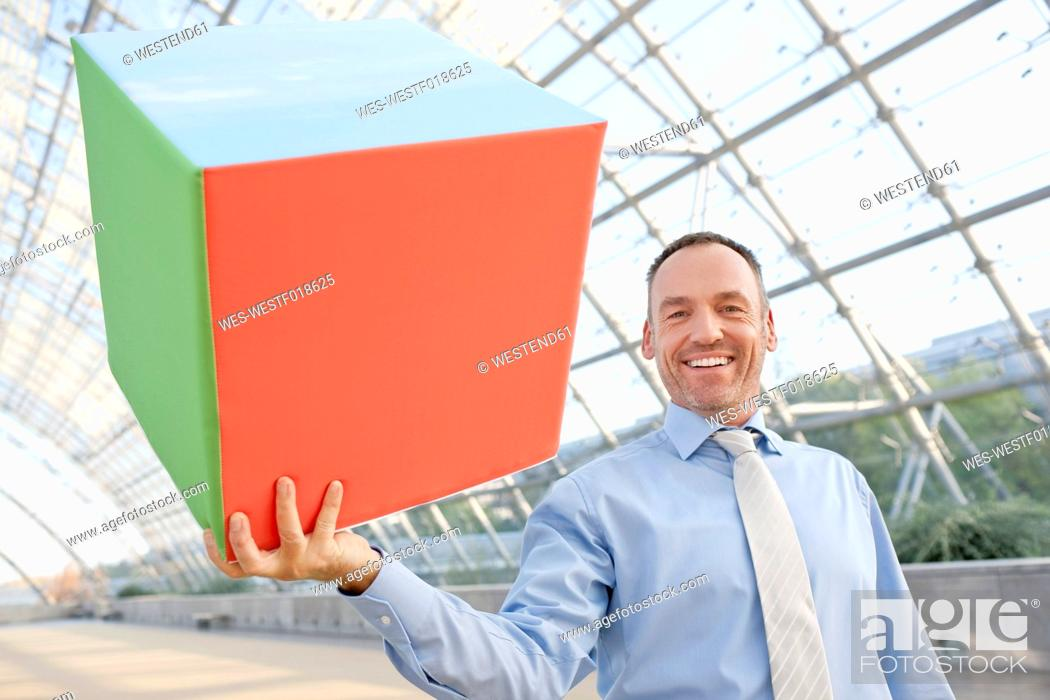 Stock Photo: Germany, Leipzig, Businessman holding cube, smiling.