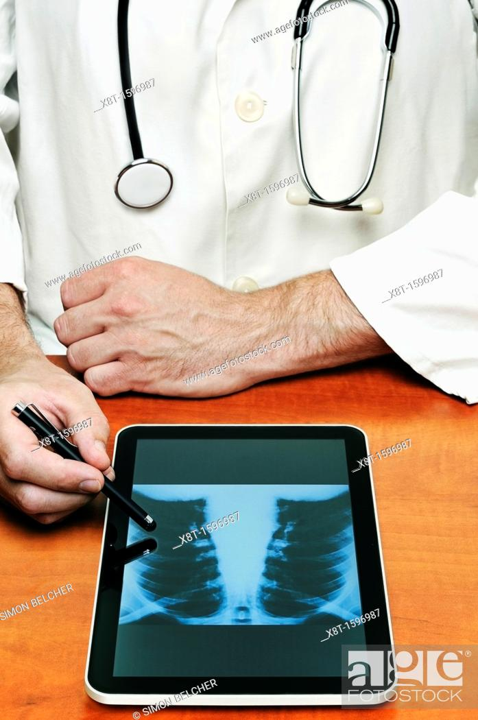 Stock Photo: Doctor Using a Digital Tablet to Examine a Chest X Ray.
