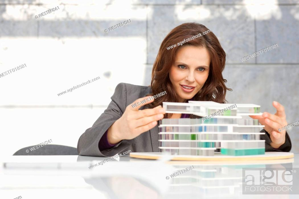 Stock Photo: Germany, Leipzig, Businesswoman looking at architectural model.