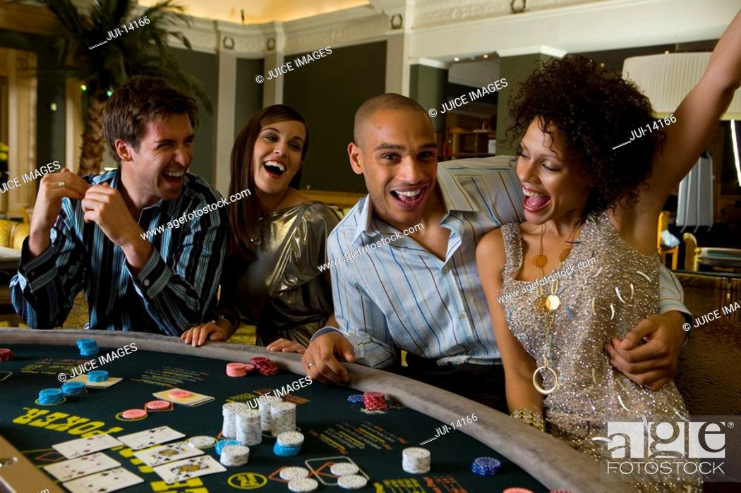 Stock Photo: Young couple gambling at poker table in casino, woman with arm raised, portrait of man.