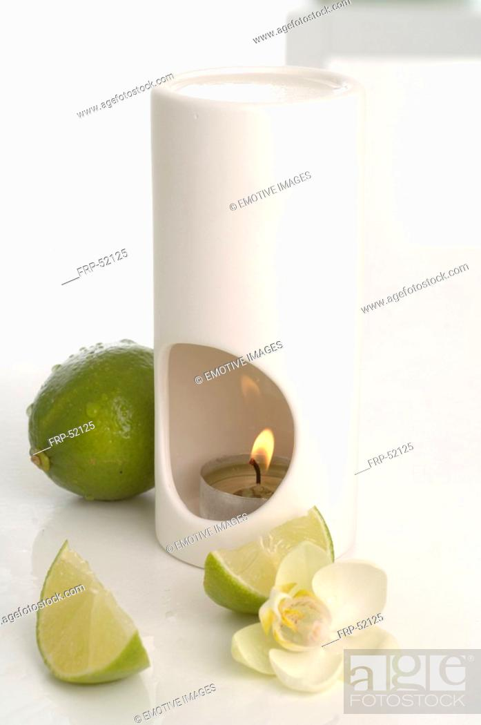 Stock Photo: Aroma lamp, limes and orchid blossoms.