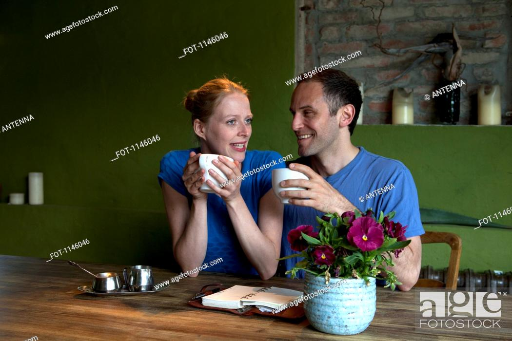 Stock Photo: A couple sitting at a dining table with a personal organizer, talking over coffee.
