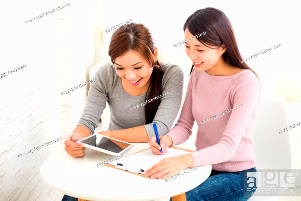 Stock Photo: Two young girls use of the tablet pc and taking note on clipboard.