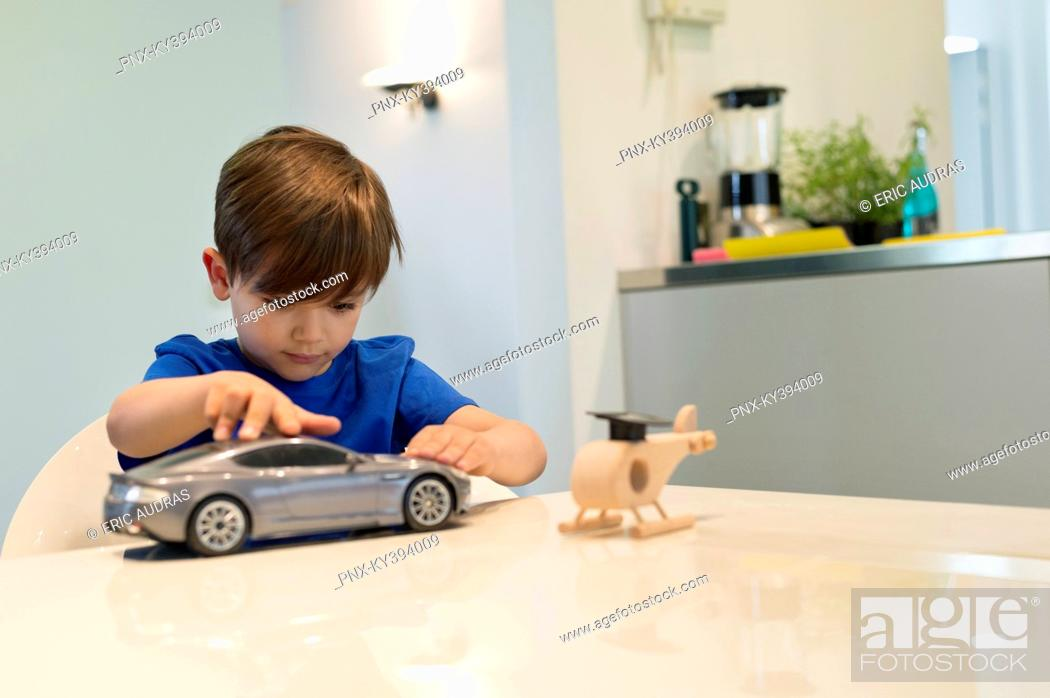 Stock Photo: Boy playing with a toy car.