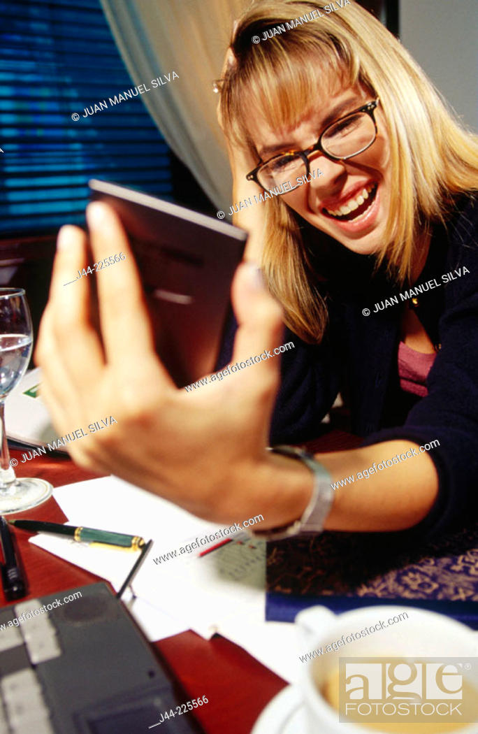 Stock Photo: Businesswoman working on a desk with handheld in an office.