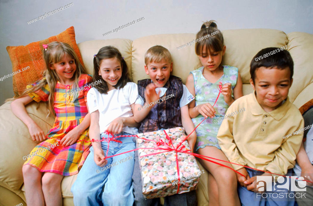 Stock Photo: Children sitting on a couch at a birthday party.
