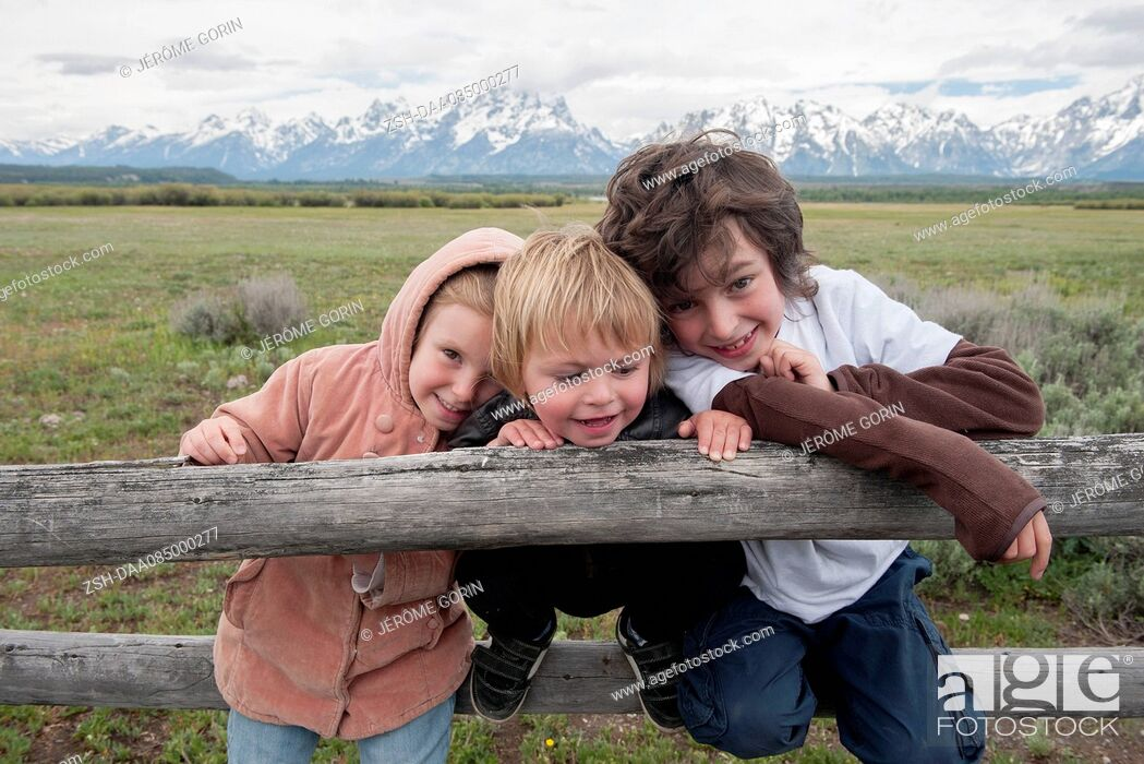 Stock Photo: Children leaning against fence in Grand Teton National Park, Wyoming, USA.