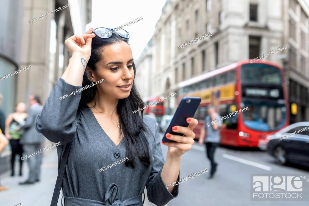 Stock Photo: Business woman near a busy street checking her smartphone, London, UK.