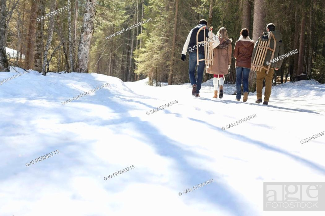 Stock Photo: Couples carrying sleds in snowy woods.