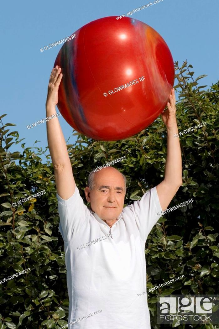 Stock Photo: Portrait of a senior man exercising with a fitness ball.