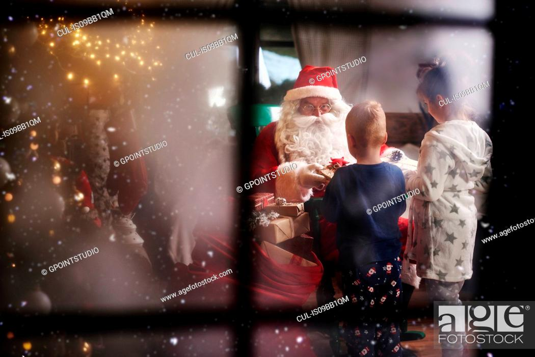 Stock Photo: Young girl and boy receiving gifts from Santa, viewed through window.