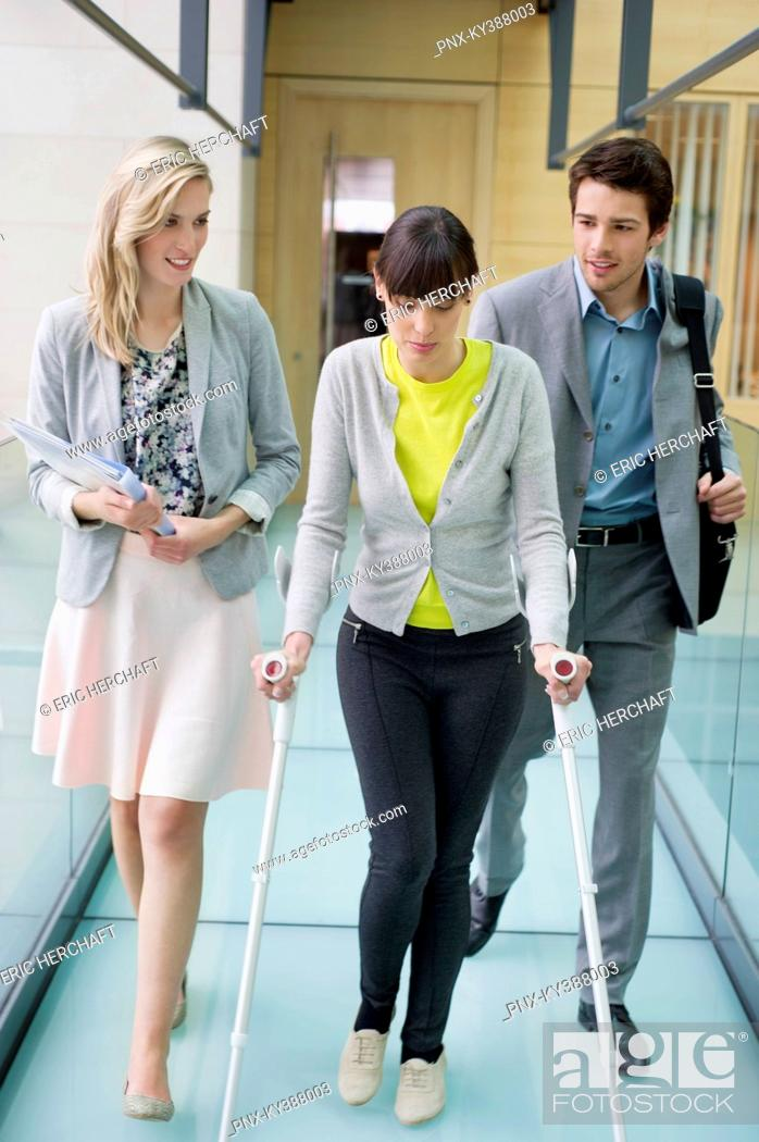 Stock Photo: Disable woman walking with business executives in an office corridor.