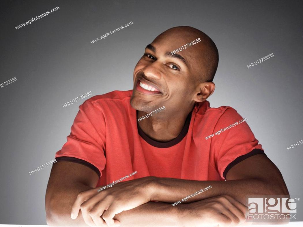 Stock Photo: Young man smiling (portrait).