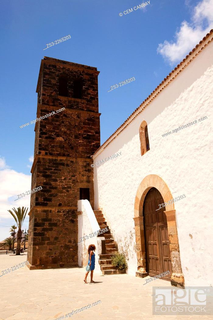Stock Photo: Woman walking near the de Nuestra Senora de la Candelaria Church with its lava stone bell tower, La Oliva, Fuerteventura, Spain, Europe.