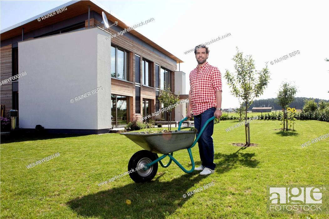 Stock Photo: Germany, Bavaria, Nuremberg, Mature man with wheelbarrow in garden.