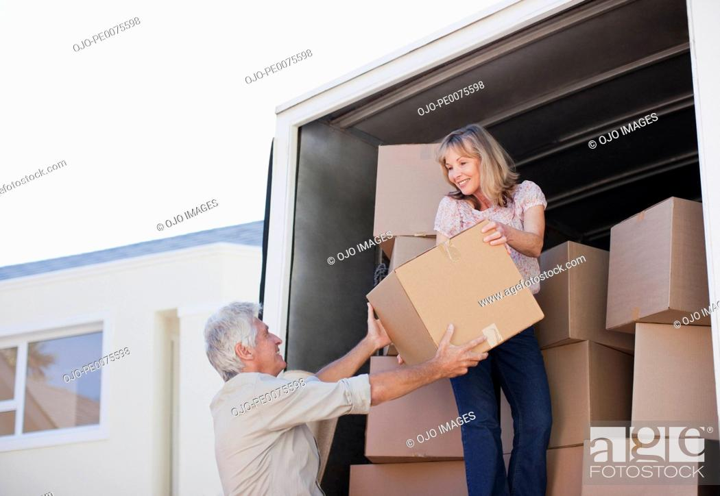 Stock Photo: Couple unloading boxes from moving van.
