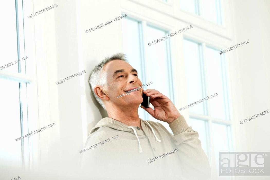 Stock Photo: Germany, Berlin, Senior man using cell phone, smiling.