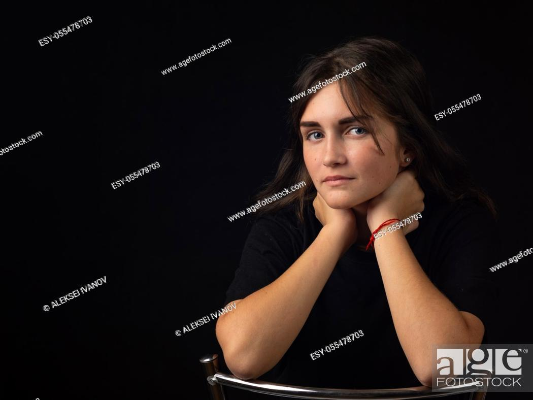 Stock Photo: Portrait of a young girl with her elbows on the back of a chair, the girl looks into the frame.