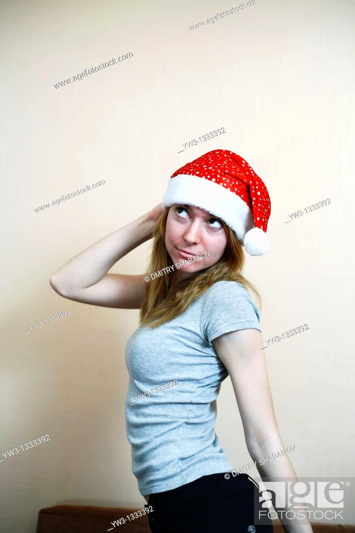 Stock Photo: pretty girl in the Christmas hat against light wall posing.