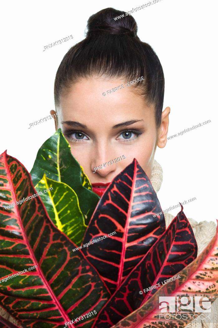 Stock Photo: Young woman holding leaves.