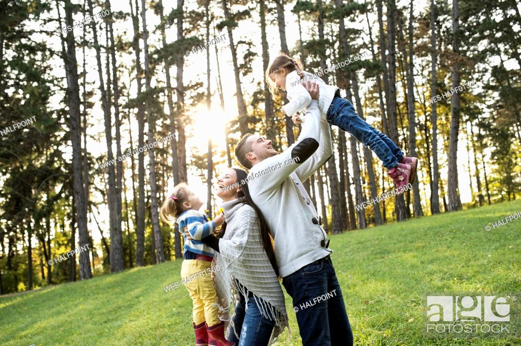 Stock Photo: Playful family with two girls in forest.