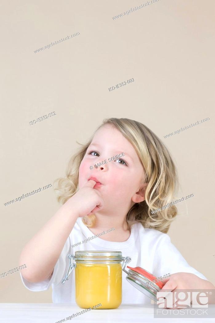 Stock Photo: Girl eating lemon curd.