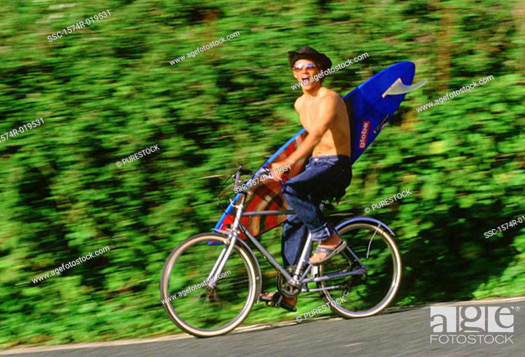 Stock Photo: Young man riding bicycle carrying surfboard.