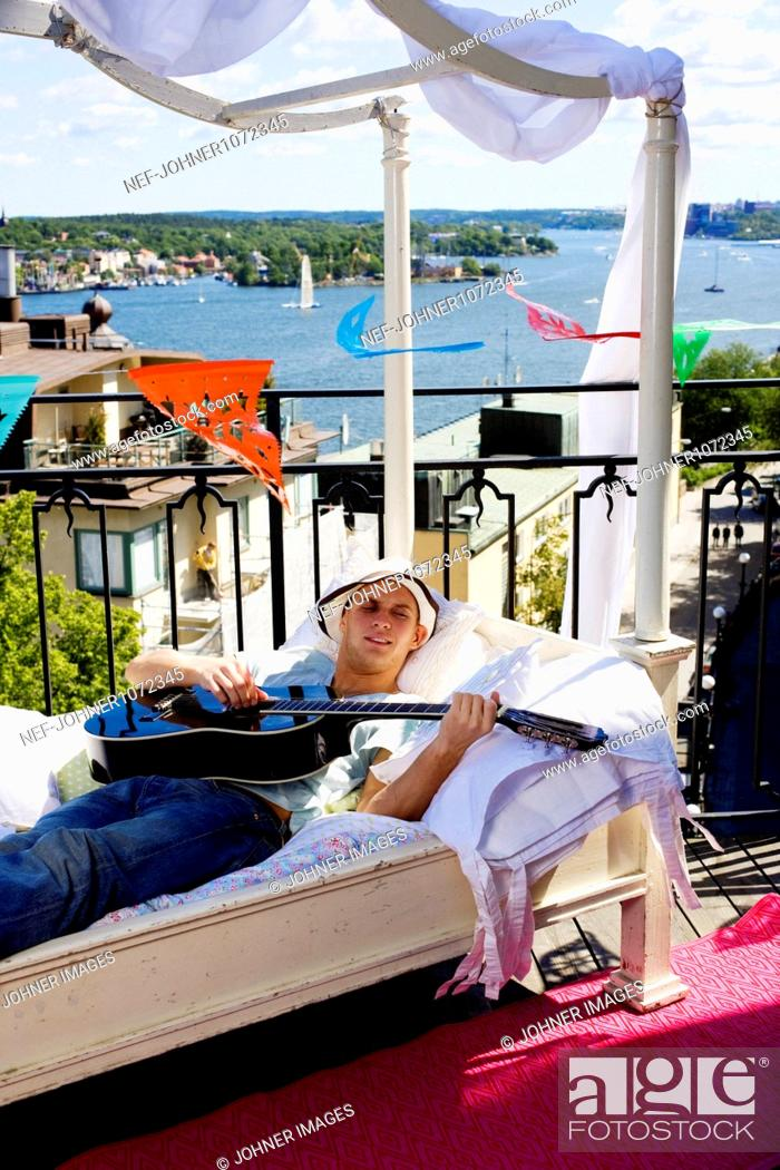 Imagen: Man playing guitar on balcony.